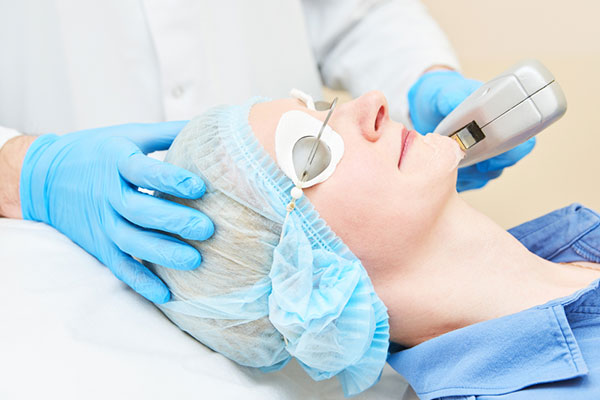 doctor doing an IPL photofacial on woman